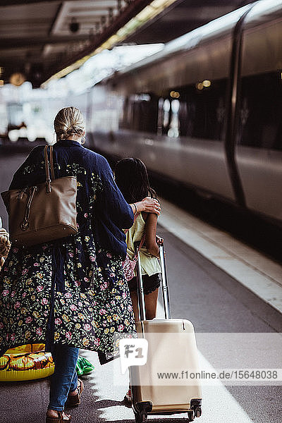 Rear view of mother and daughter walking with luggage on railroad station platform