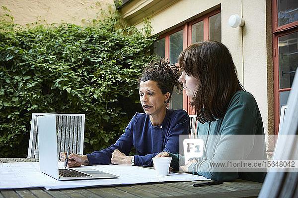 Ingenieurinnen planen über Laptop am Tisch im Hinterhof