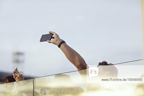 Niedrigwinkelansicht von Kollegen  die mit einem Smartphone fotografieren  während sie auf der Terrasse eine Büroparty feiern