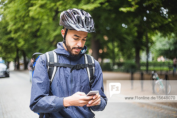 Food delivery man using mobile phone on street in city