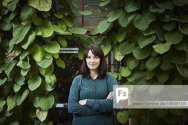 Porträt einer selbstbewussten Architektin  die sich im Hinterhof gegen Kletterpflanzen stellt
