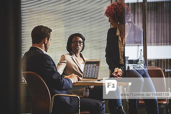 Reife Anwältin diskutiert mit Kollegen am Konferenztisch im Sitzungssaal