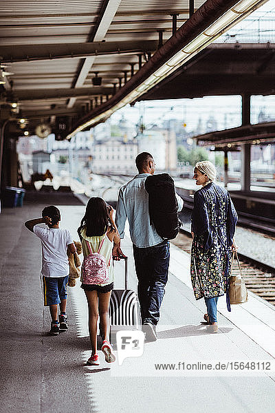 Man with luggage talking to family while walking at train station