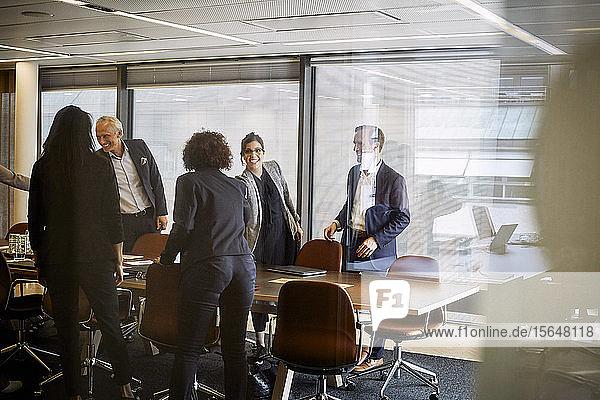 Lächelnde Anwälte und Anwältinnen beim Händeschütteln  während sie sich im Sitzungssaal im Büro begrüßen