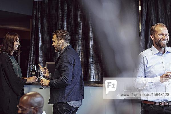 Männliche und weibliche Kollegen diskutieren bei einer Bürokonferenz bei einem Drink