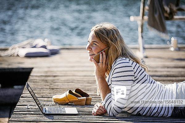 Lächelnde Frau mit Laptop  die mit einem Smartphone telefoniert  während sie über einem Holzsteg liegt