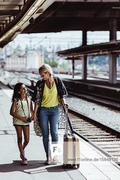Mutter und Tochter in voller Länge mit Gepäck zu Fuß am Bahnhof