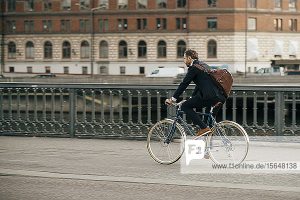 Full length of businessman riding bicycle on street in city