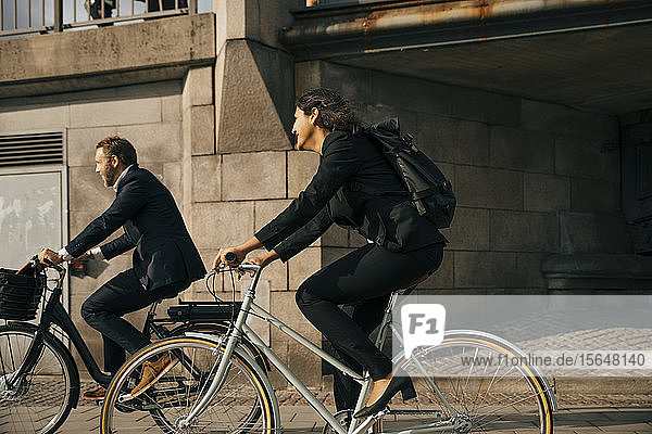 Side view of businessman and businesswoman riding bicycles on street in city