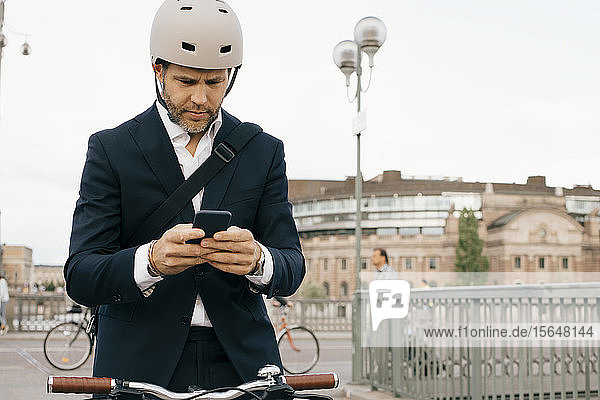 Businessman using mobile phone while standing with bicycle on bridge in city