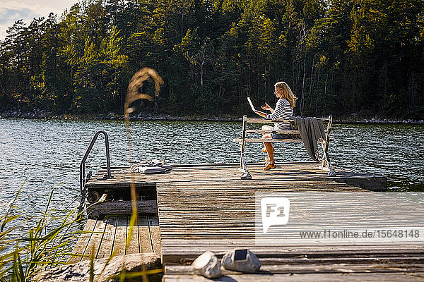 Mid adult woman doing video call on laptop while sitting on bench over wooden pier against lake in forest