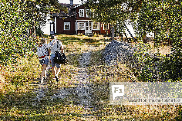 Male and female partners walking on pathway towards house during summer vacation