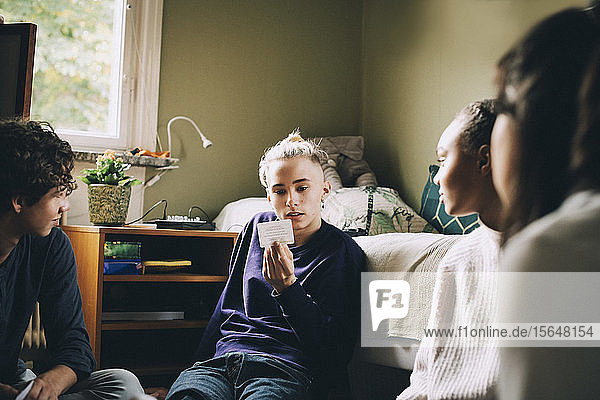 Friends looking at teenage boy reading placard while playing in bedroom