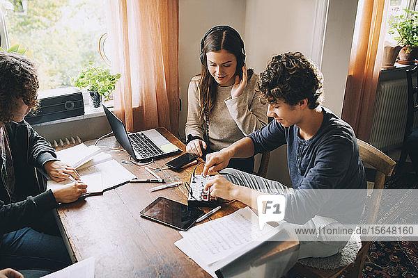 Hochwinkelansicht von Freunden mit Tonmischpult  während ein Teenager am Tisch im Zimmer lernt