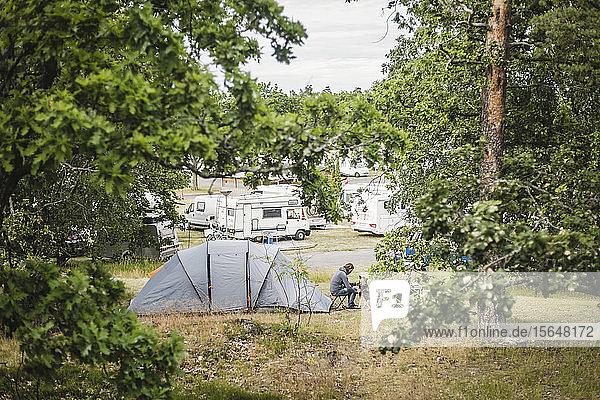Mann spielt mit Hund im Zelt auf dem Campingplatz