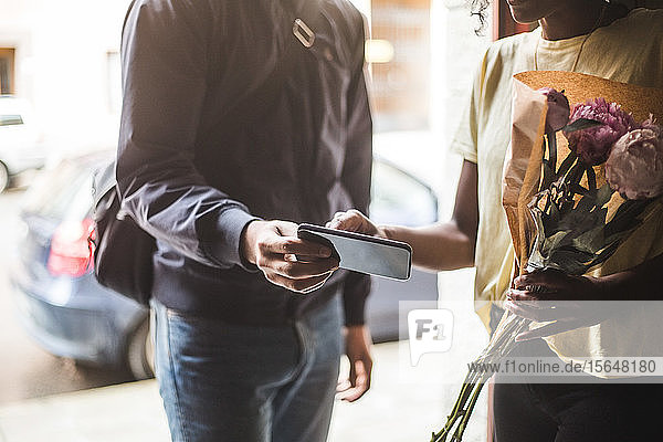 Midsection of delivery man taking sign from customer while delivering bouquet