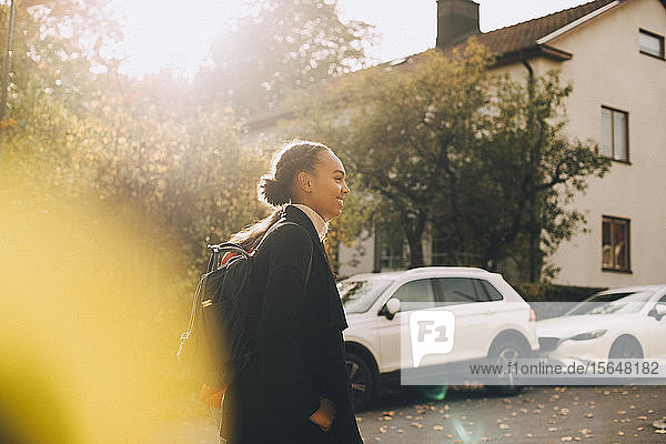 Side view of teenage girls walking against cars and house during autumn