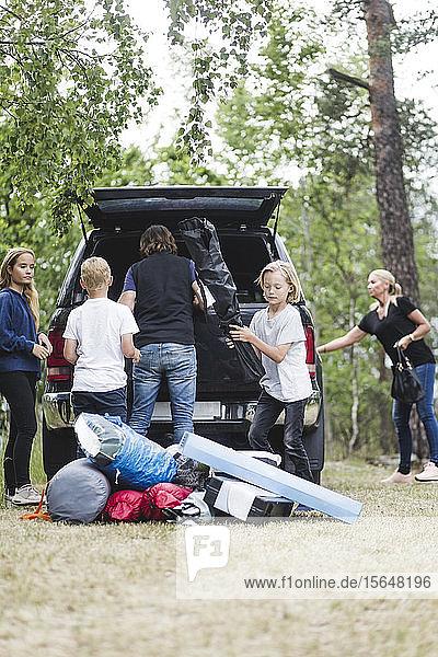 Camping-Familie entlädt Gepäck aus dem Kofferraum eines Autos im Wald