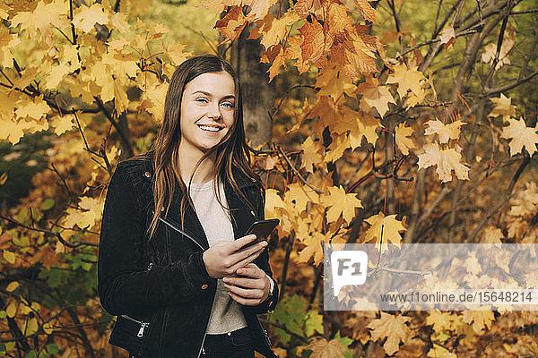 Porträt eines lächelnden Teenager-Mädchens mit Handy  das im Herbst an Bäumen steht