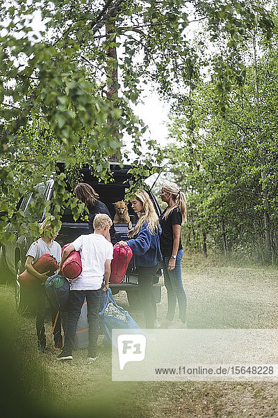 Family unloading luggage from car at camping site