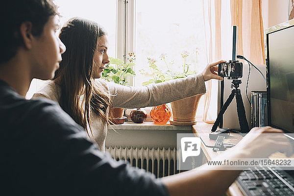 Teenagerin  die ein Smartphone auf einem Stativ einstellt  während sie mit einem Freund zu Hause am Computer sitzt