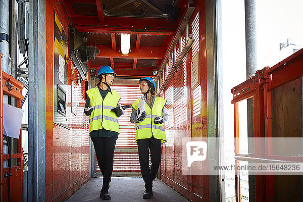 Full length of female engineers discussing while walking in freight elevator at construction site