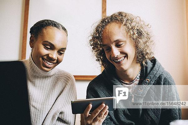 Männliche und weibliche Teenager lächeln  während sie im Zimmer auf ein Smartphone schauen
