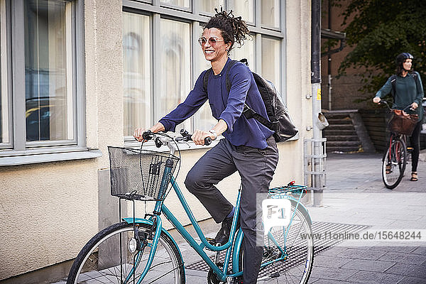 Smiling young female architect riding bicycle on street in city