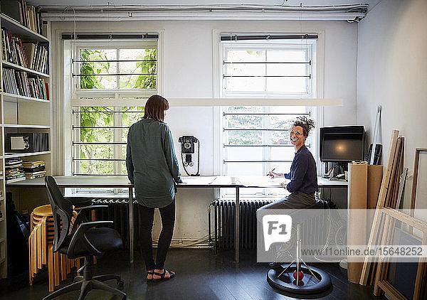 Lächelnde Architektin mit Mitarbeiterin am Tisch im Büro