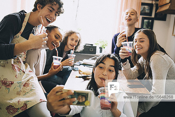 Teenage girl taking selfie with friends through mobile phone while enjoying smoothie at home