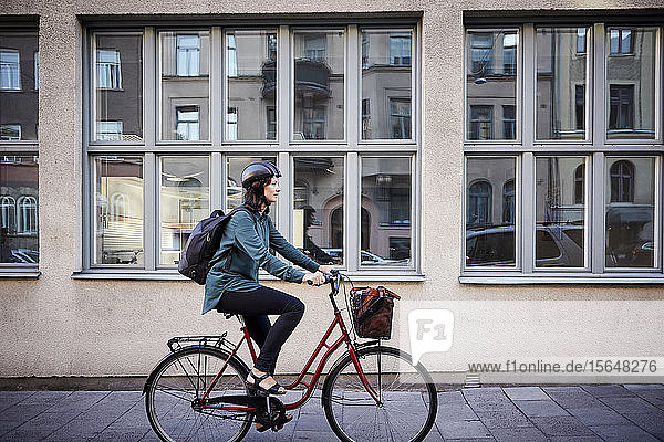Side view of female engineer riding bicycle on street by building in city