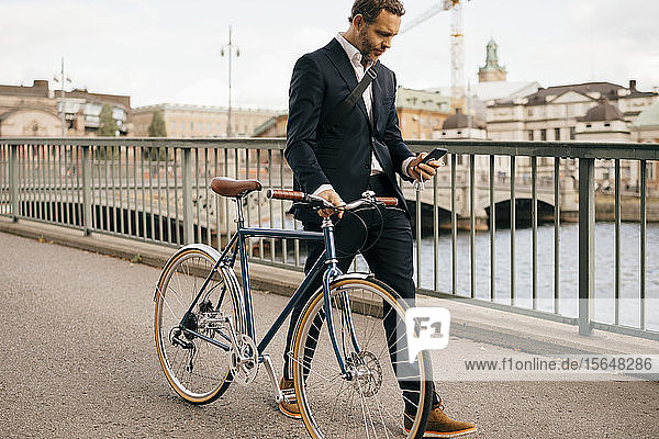 Confident businessman using smart phone while walking with bicycle on bridge in city