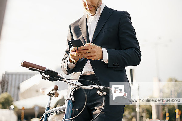Midsection of businessman using mobile phone while standing by bicycle in city