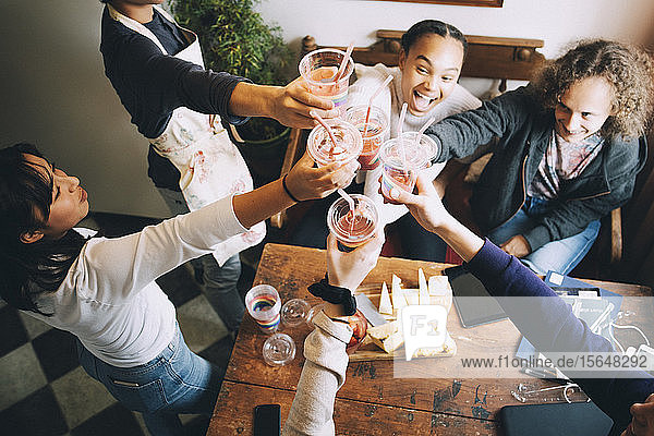 High angle view of multi-ethnic friends toasting smoothies over table at home