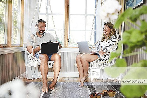 Lächelndes Paar benutzt Laptops  während es auf einer Seilschaukel im Blockhaus sitzt