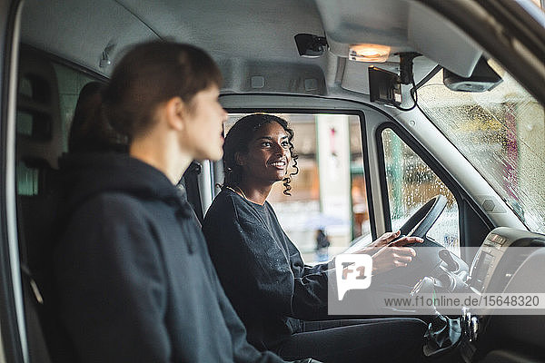 Female mover looking in rear-view mirror while driving truck