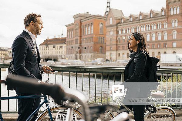 Smiling businesswoman talking with businessman on bridge while biking in city