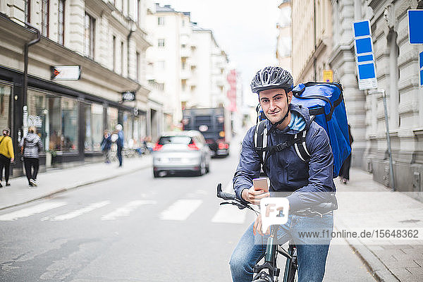 Portrait of confident food delivery man with bicycle on street in city