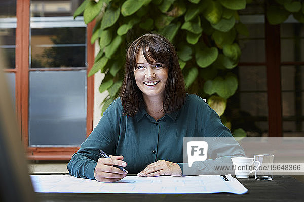 Portrait of smiling female architect with blueprint at table in backyard