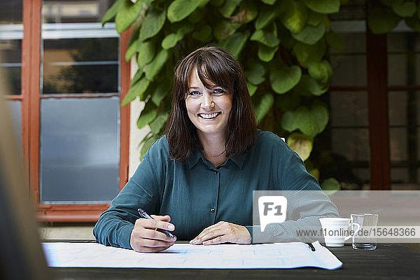 Porträt einer lächelnden Architektin mit Blaupause am Tisch im Hinterhof