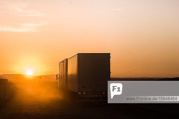 Silhouetten-Lkw bei Sonnenuntergang auf der Straße