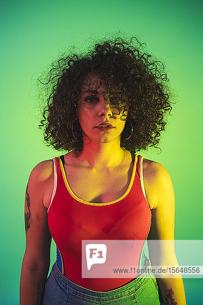 Young woman in red tank top posing against green background