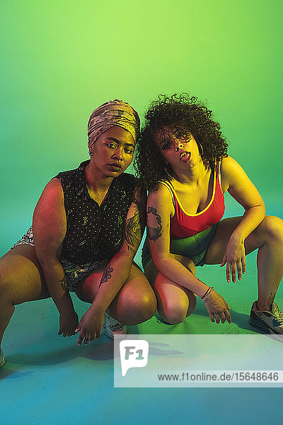 Young women squatting against green background