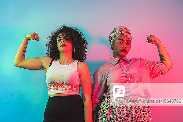Young women flexing arms against blue and pink background