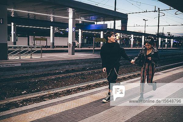 Junges Paar rennt auf dem Bahnsteig im Bahnhof  Mailand  Italien