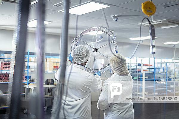 Arbeiter bei der Montage der OP-Beleuchtung in einer Fabrik für Elektronikmontage
