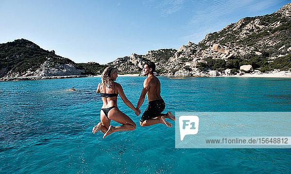 Young couple jumping into sea from yacht  La Maddalena island  Sardegna  Italy