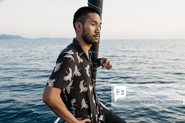 Junger Mann auf Segelboot schaut in die Ferne,  Italien