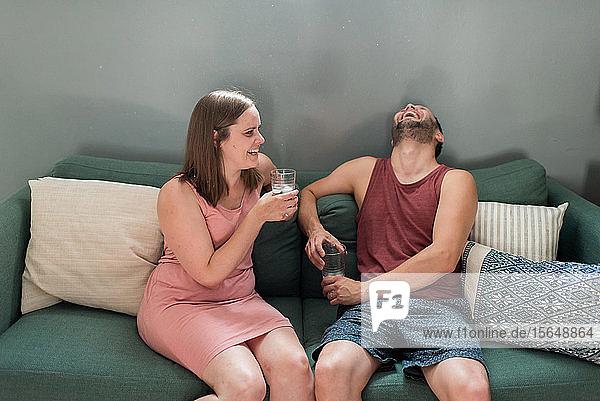 Paar redet und lacht zu Hause auf dem Sofa