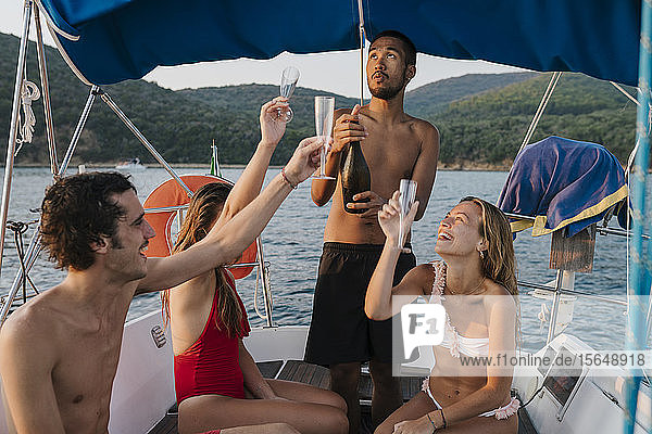 Friends toasting with champagne on sailboat  Italy